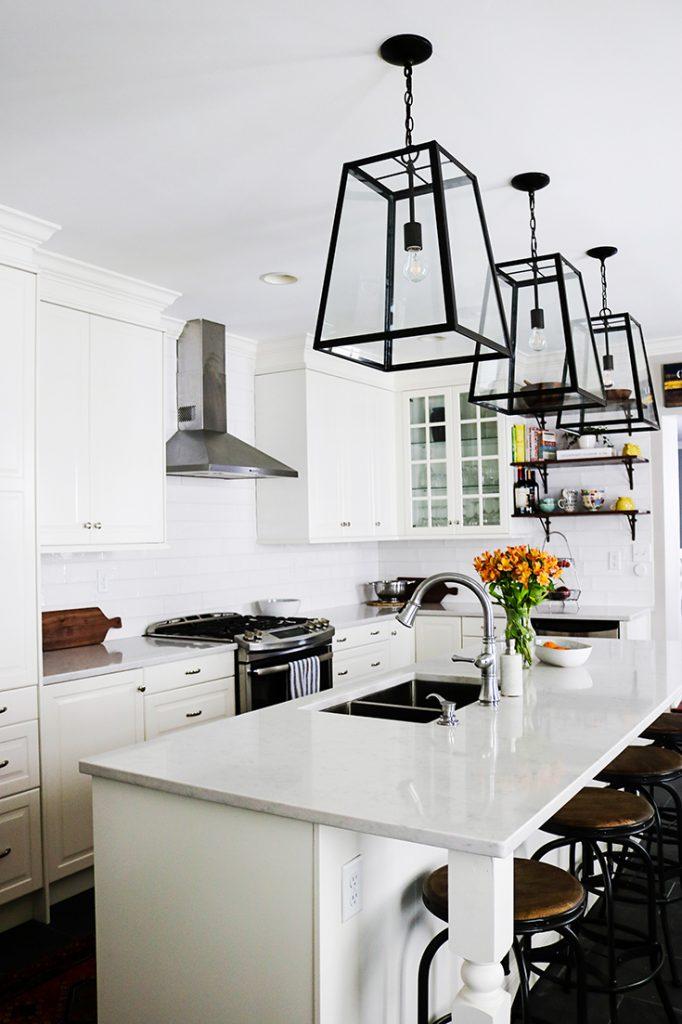 white kitchen cabinets, white quartz countertops, lantern style pendant lights, subway tile
