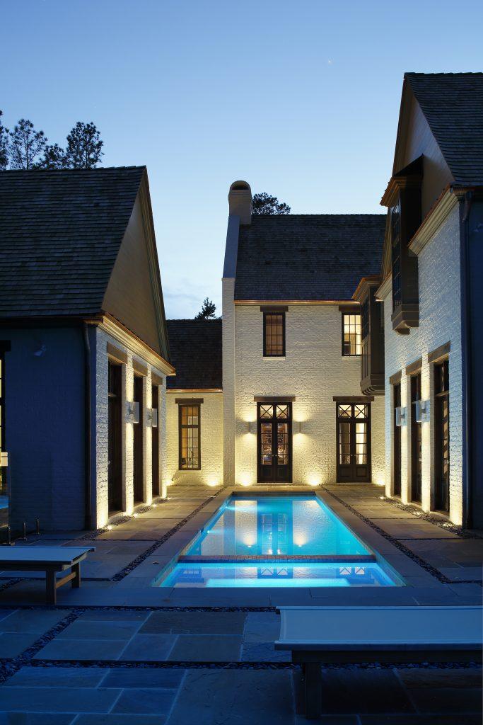 منظره شبانه استخر مستطیل شکل خانه سفید رنگ