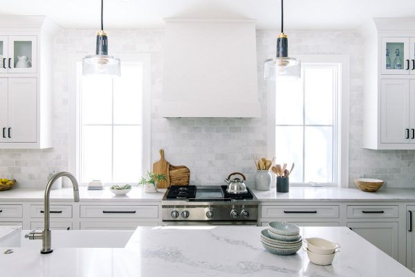 white kitchen windows by hood marble backsplash