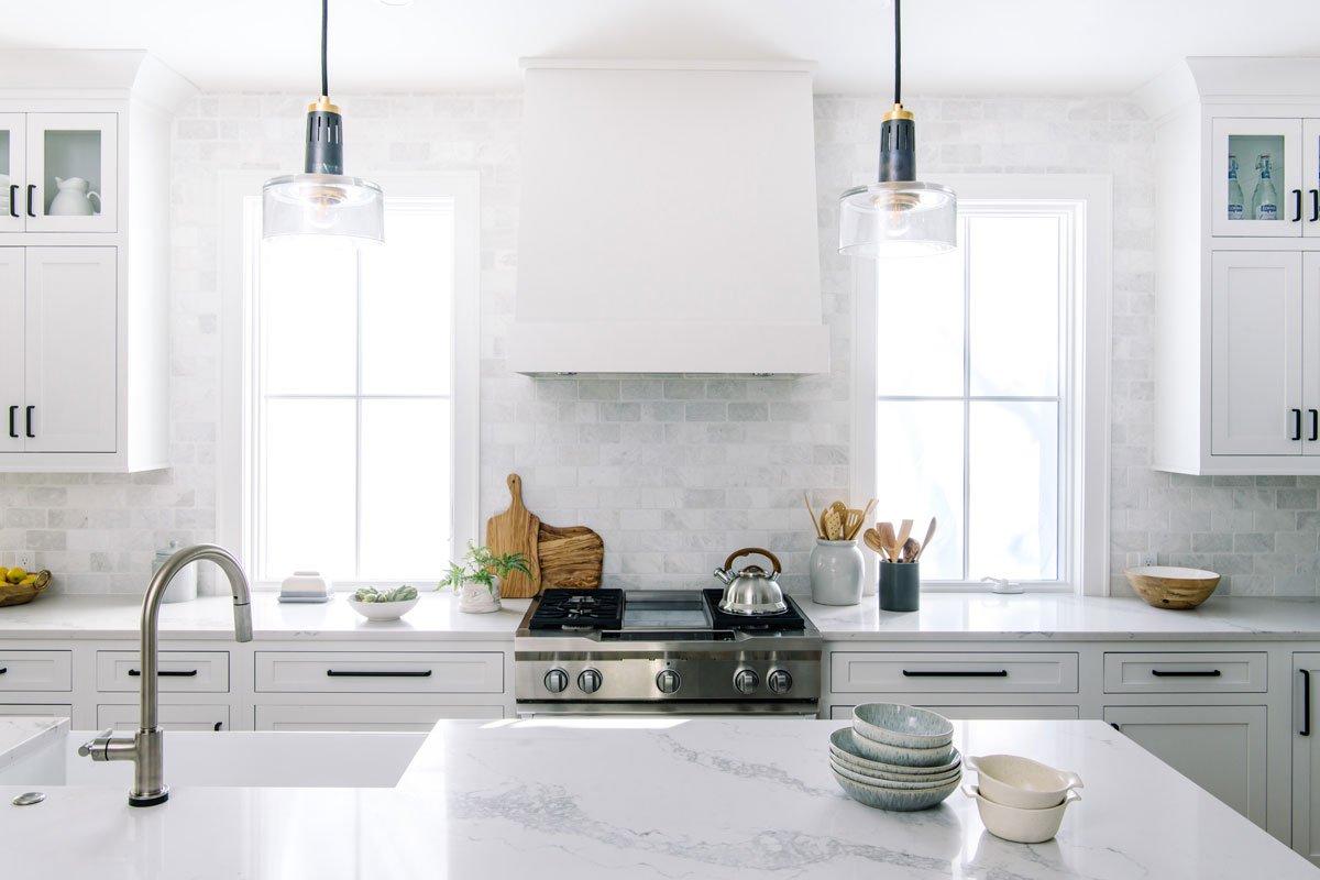 white kitchen windows by hood marble backsplash