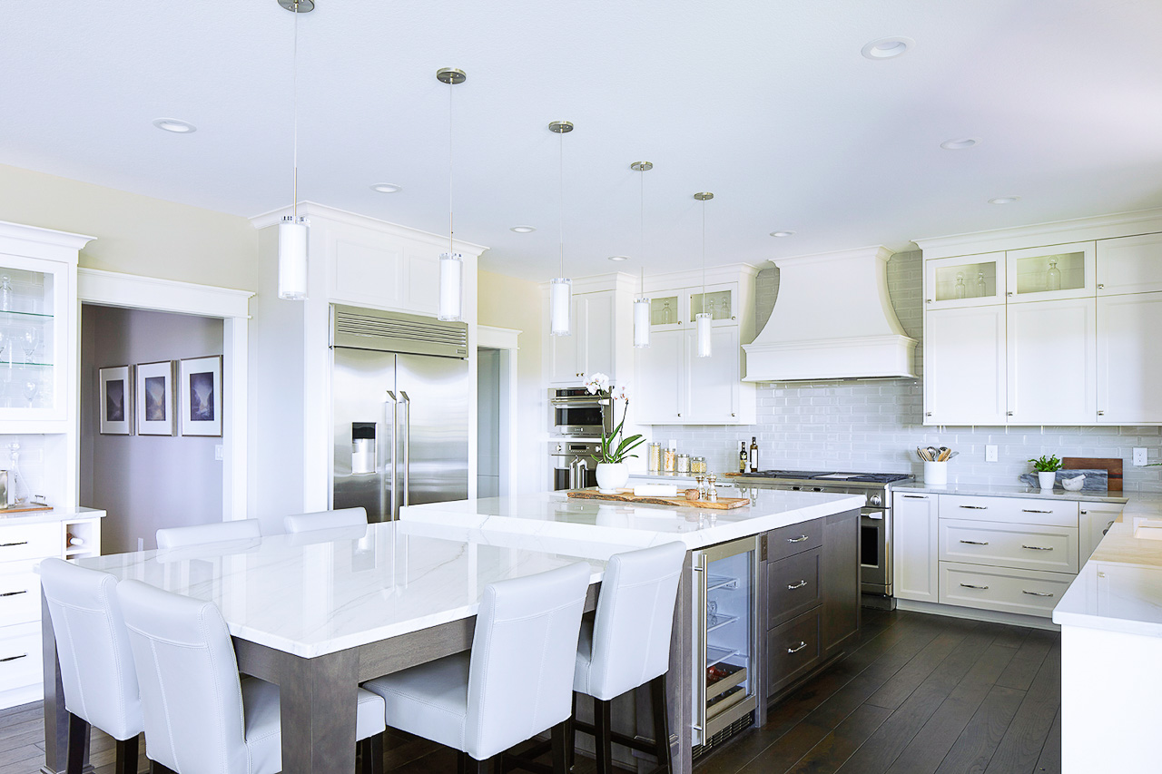 Large white kitchen with quartzite drop down island by Jillian Lare Interior Design